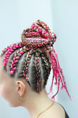 hairstyle in African style, thin plaits go to the tail, patterns from hair, hair texture close-up