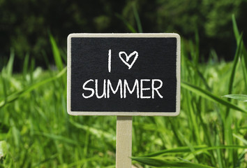 I LOVE SUMMER written in chalkboard. Sign on a green lawn. Photo stock.