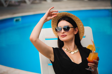 Young tan model in stylish summer outfit enjoying pool party , holding tasty alcohol cocktail .