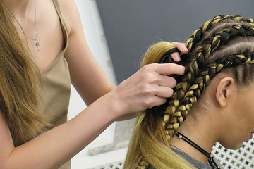 process of braiding African thick plaits in the beauty salon, studio afro hairstyles