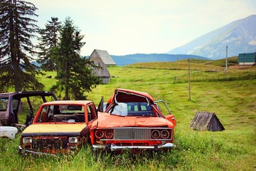 Four broken vehicles parked at the roadside on a green meadow in the background are meadows mountains and old wooden huts to see