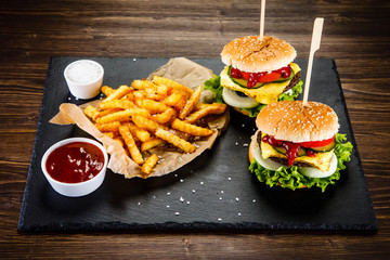 Tasty cheeseburgers with french fries served on fashionable black desk