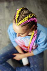spit with kanekalon, fashionable youth hair style on the head of a girl close-up