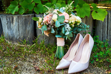 Beautiful wedding bouquet of pink and white roses and beige shiny bride shoes outdoors, copy space. Wedding morning preparation. Bride accessories. Bridal bouquet and shoes