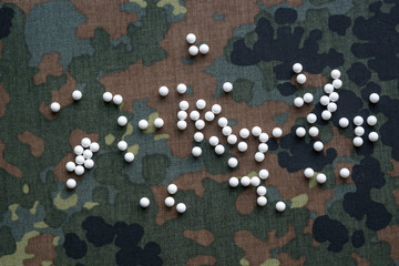 airsoft balls bbs are scattered on the background of camouflage fabric top view