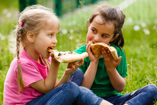 Two girls sitting and eating pizza