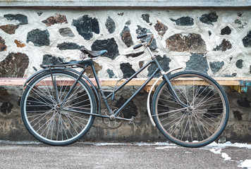 Vintage bicycle on the stone wall background