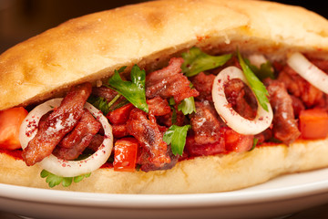 Dish in pita bread with meat, tomato, onions and parsley