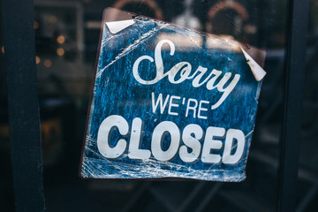 Inscription on a door: Sorry we are closed. Conceptual photo or table on door with information of work. Announcement or work schedule