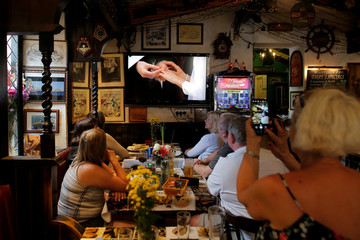 British tourists watch as Britain's Prince Harry places the wedding ring on Meghan Markle's finger during their wedding, on a television in a restaurant in the British overseas territory of Gibraltar