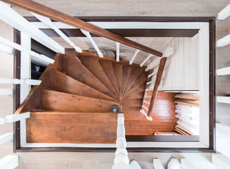 A wooden spiral staircase with rails between the floors in a private house. Interiors geometry