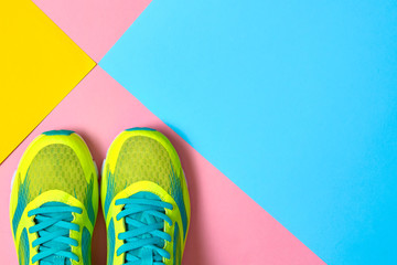 Pair of sport shoes on colorful background. New sneakers on pink, blue and yellow background, copy space. Overhead shot of running shoes. Top view, flat lay