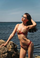 sexy woman with dark hair in luxurious bikini relaxing on the beach