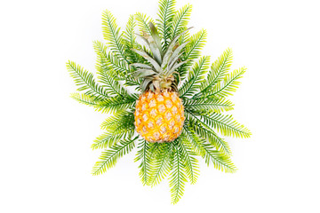 Summer holiday background. Tropical plant leaves and pineapple on yellow background. Flat lay