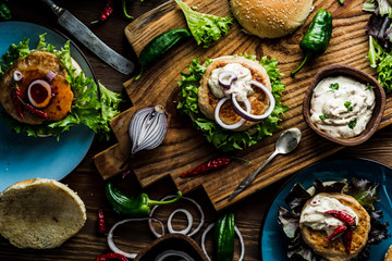 Chicken burgers with fresh salad, onion, peppers and mayonnaise sauce. Overhead view and dark, wooden background.