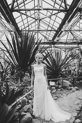 Serious woman portrait handsome bride in a wedding dress is standing on the background of Botanical garden full of cactus. Black and white photo.