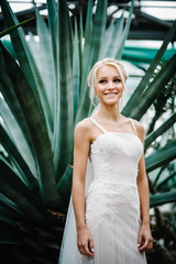 Portrait attractive blonde bride standing in a wedding dress on the background of greenery. Woman stand in the Botanical green garden full of greenery. Wedding ceremony.