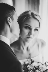 Portrait of the bride and groom near the window indoors in the rooms. Man and woman kissing. Black and white photo.