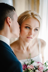 Serious portrait of the beautiful bride with a wedding bouquet of flowers and groom near the window indoors in the rooms. Man and woman kissing.