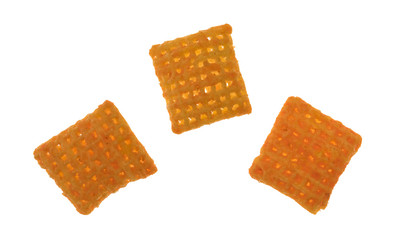 Top view of three cheddar cheese crispy rice crackers on a white background.