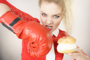Woman fighting off bad food, boxing cream puff cake