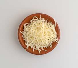 Top view of sharp white cheddar cheese in a small bowl on a counter top.