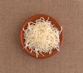 Top view of sharp white cheddar cheese in a small bowl on a brown tablecloth.