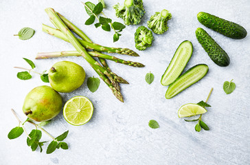An Arrangement of Green Vegetables,  Fruits and Herbs; asparagus, broccoli, cucumber, pears, lime, mint; flatlay