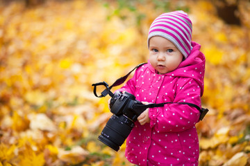 Little kid is playing with camera and taking photo of autumn nature as master. Baby is in autumn park. Girl is dressed in warm hat and jacket.
