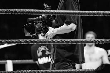 Garden Poster Martial arts cameraman with video camera in ring during competition MMA black and white photo