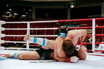MMA fight two fighters on floor ring competition in martial arts
