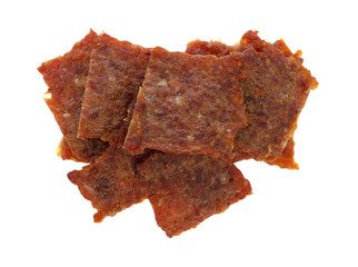 Top view of several pieces of pork jerky on a white background.