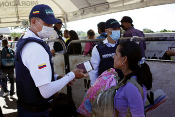 Colombian migration officers inspect the IDs of the people crossing the Colombian-Venezuelan border over the Simon Bolivar international bridge in San Antonio del Tachira