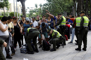 Colombian police officers frisk people and inspect their luggage as Venezuelans queue outside an exchange house in Cucuta