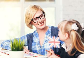 Smiling blonde English educator wears eyeglasses studying with kid girl, language learning with...