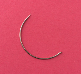 Curved upholstery cloth needle on a red paper background.