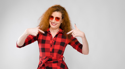 Young red-haired girl in a red checkered shirt. Young girl showing thumb and forefinger. Young girl in red glasses
