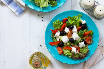 Greek salad with fresh vegetables, feta cheese and black olives in a blue plate on white wooden table. Copy space, top view flat lay background.