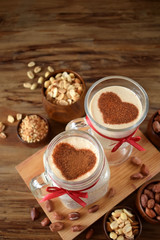Milkshake decorated with cinnamon heart in glass vessels. Top view. Peanuts are around
