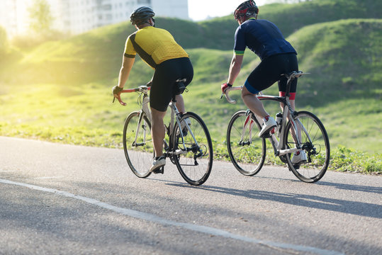 Active male athletes riding bicycles on an open country road