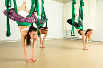 Young woman performing aerial yoga exercise