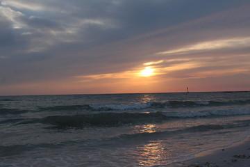 Pastel colorful sunset horizon over the ocean waves crashing into the beach shoreline