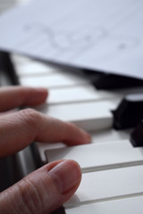 Black and white piano keys and musician's hands playing a tune