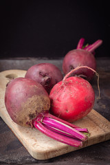 Fresh beets on a wooden pan on dark background