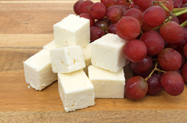 Feta cheese chunks with fresh grapes on a wood cheese board side view.