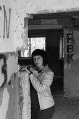 Black and white photo. A young woman standing against the wall in a ruined old building.