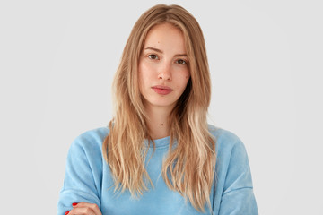 Horizontal shot of attractive young European female student with long hair, looks seriously at camera, poses for university graduation album, wears loose blue sweater, stands against white background
