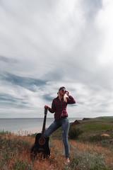 girl with a guitar on a cliff near the ocean