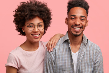 Photo of friendly African American male and female stand close to each other, have broad smiles on faces, have date together, pose against pink background. Beautiful dark skinned woman and her friend
