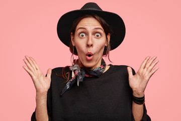 Emotional female adult gestures with stunned expression, stares at camera, wears black elegant hat, being surprised by unexpected gift, poses against pink background. People and emotions concept
